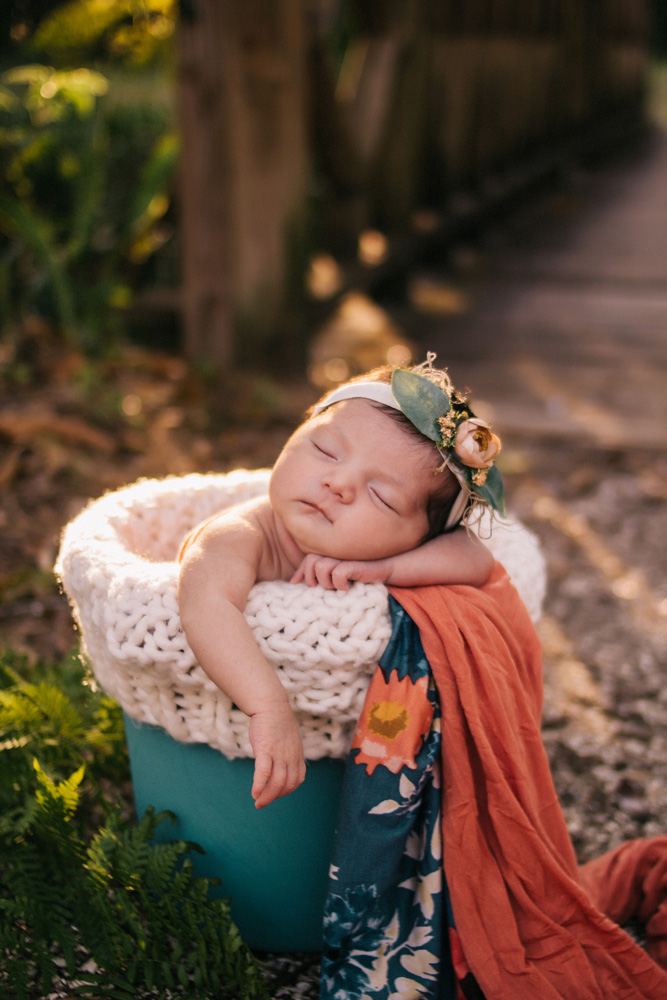 Newborn girl propped up in a blue bucket with pink and blue fabric and a knit layer. She is wearing a floral headband and is outside at Koreshan park in estero florida in front of a bridge. Outdoor newborn photographer fort myers Florida